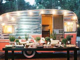 Air stream vintage trailer in pink and silver decorated with string lighting behind a rustic dessert table.