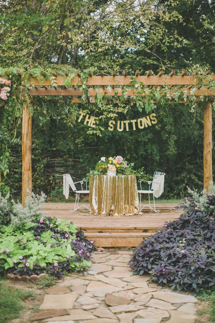 The newlyweds had the seats of honor beneath a banner with their new last name in a vine-draped pergola.