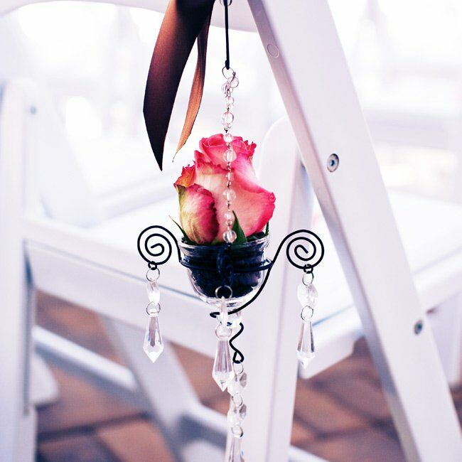 Small, wrought iron chandeliers with roses and dangling crystals hung from chairs along the aisle.