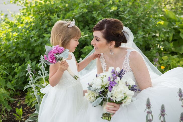 Elena kneeled down to see the flower girl, who wore a simple white dress with lace ribbon wrapped around her waist. The little girl wore a silver tiara in her hair and held onto a purple bunch of roses accented with dusty miller.