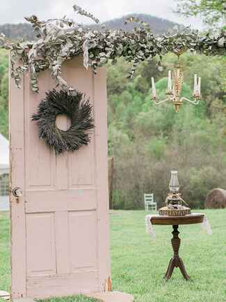 A rustic painted wooden door wedding arch with lavender wreath