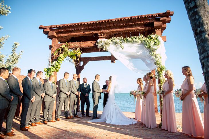 Sarah and Morten made their beach front wedding feel romantic and lush by draping arrangements peonies and greens alongside white fabric from the wedding arch.