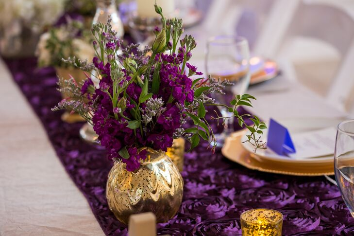 purple floral centerpiece in distressed gold vase