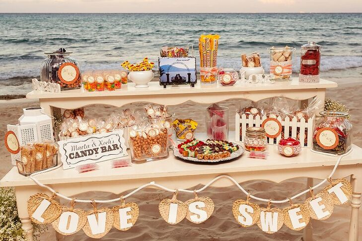 A candy bar added a sweet touch to Marta and Jose Luis's reception at Le Reve Hotel and Spa in Playa del Carmen, Mexico. They offered a variety of treats and snacks for their guests, labeled with their custom monogram.