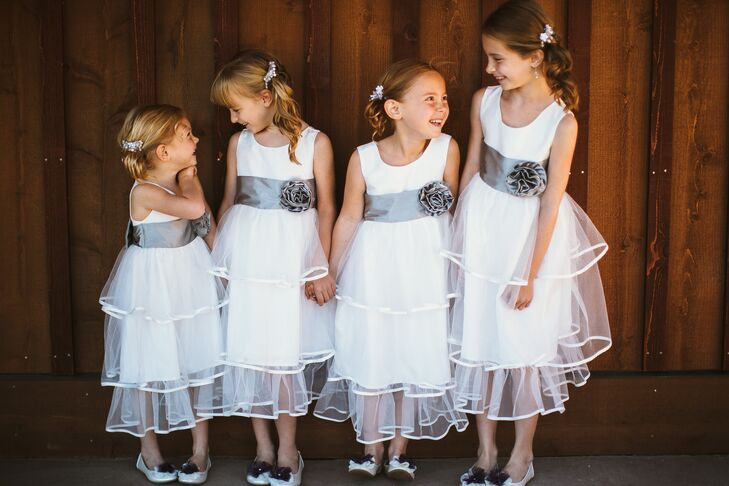 The four flower girls stood in a line, wearing their white dresses with ruffled tulle skirt overlays. They each had a silver sash accented with a fabric flower wrapped around their waists.