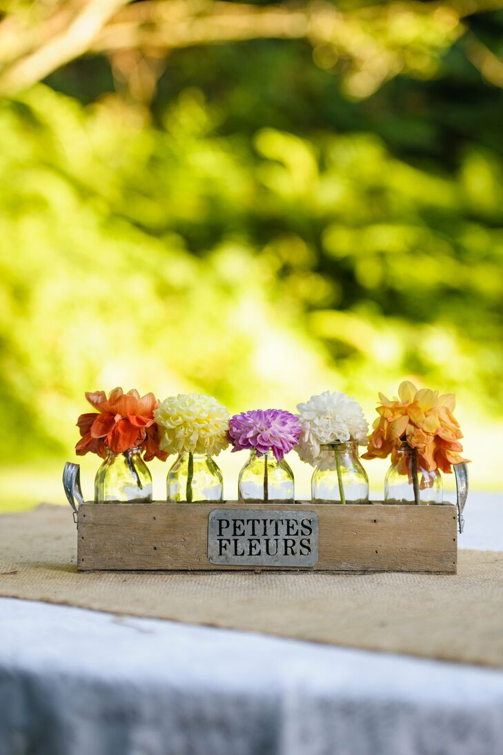 Bright zinnias and dahlias filled a row of bud vases set in an antique tray.
