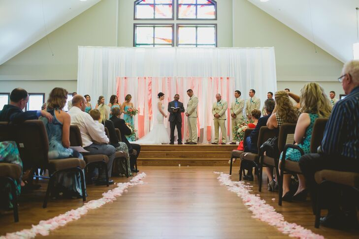 The couple exchanged their vows at Unity Church. (Cassi loved the hardwood floors and bright sanctuary.) Soft, pink rose petals lined the aisle leading up to the altar stage.