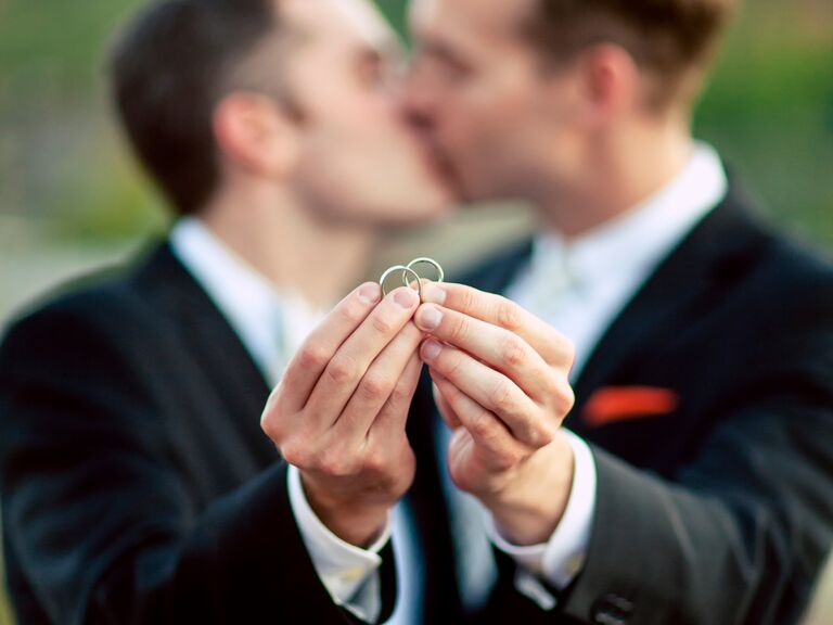 grooms holding wedding bands - Same Sex Wedding Rings