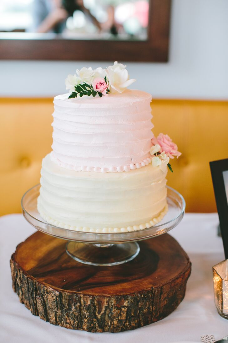 Meghan and Camron's friend made this gorgeous two-tier buttercream cake. The outside was simple with textured pink frosting on the top layer and ivory on the bottom. Fresh pink and white blooms adorned the top and side to fit the natural theme. Inside, the cake was Funfetti—Camron's favorite.