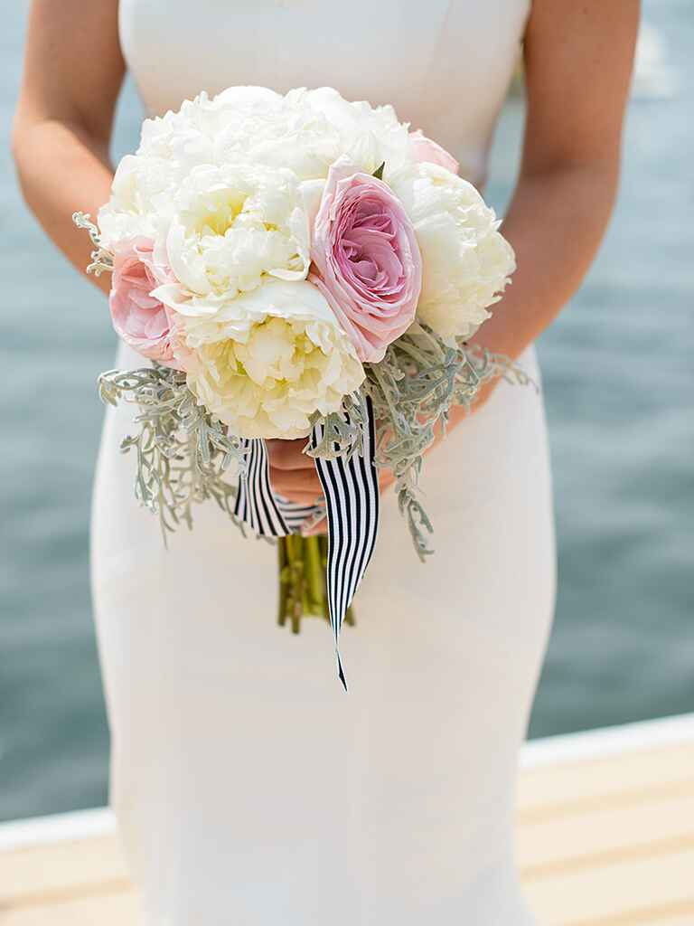 White and pink wedding bouquet wrapped with striped ribbon