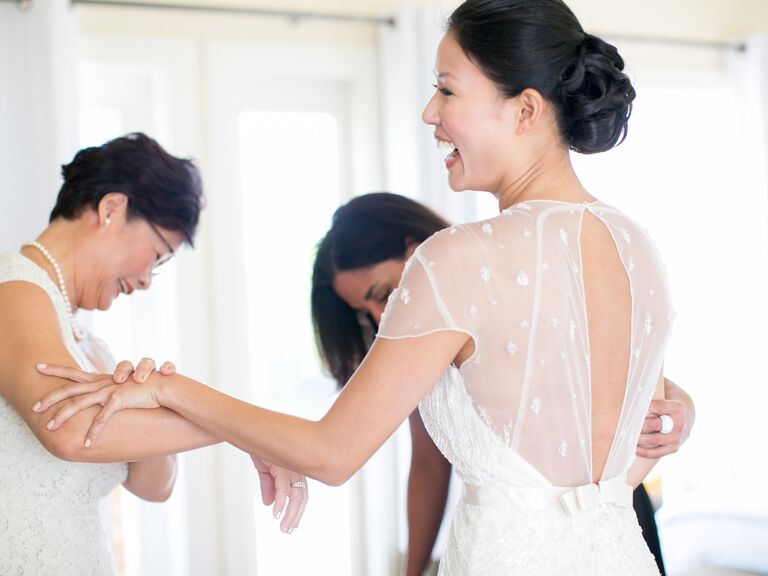 Bride with mother trying on wedding dress