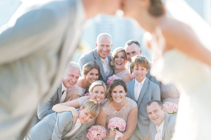 The wedding party was all smiles after the ceremony while the bride and groom shared a sweet kiss. The bridesmaids wore blush lace gowns while the groomsmen wore gray suits with blush ties.