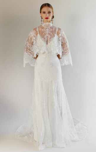 Claire Pettibone Spring 2017 fitted silhouette wedding dress of embroidered tulle with ivory cording, shown with matching cape of silver thread and clear sequins