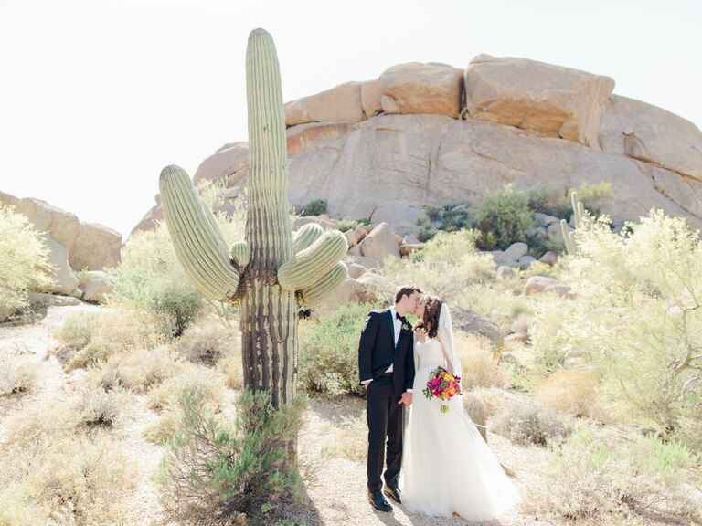 newlyweds kissing next to cactus in Arizona