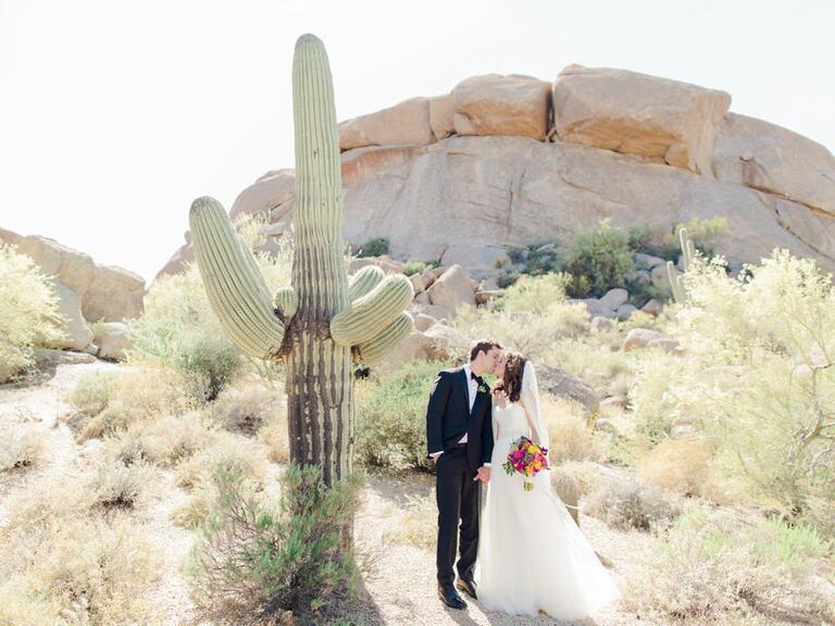 newlyweds kissing next to cactus in Arizona