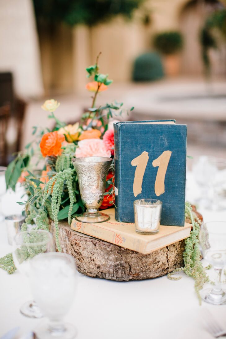 A wooden slab draped with moss held up a votive candle and vintage-style books, one of which had the number of the table displayed on the front. Each and every dining table had a mix of these elements.