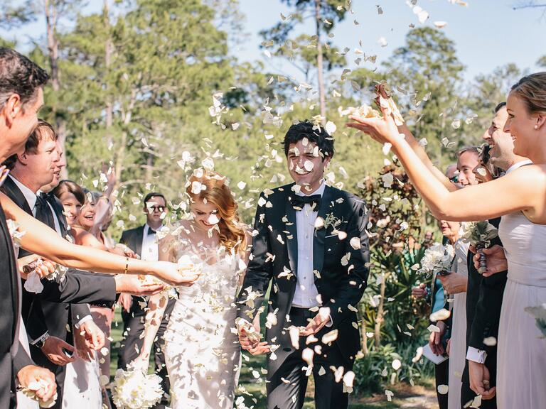 Guests throw petals as bride and groom exit