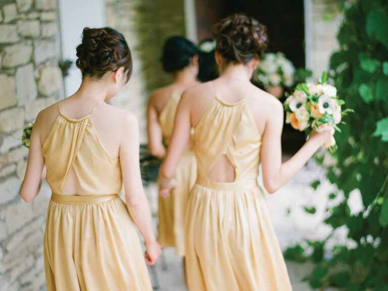 Bridesmaids in gold dresses walking to ceremony