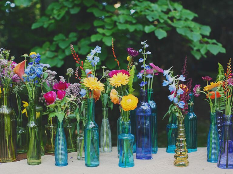 Multicolor wedding reception vases with flowers outdoors