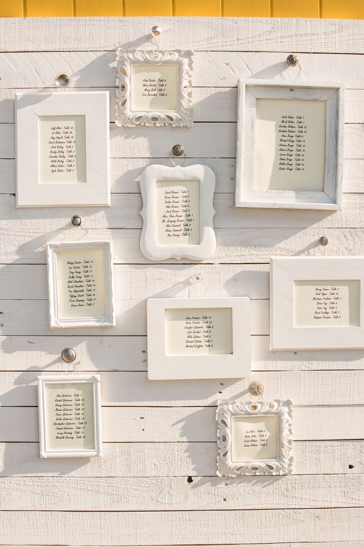 White frames in different shapes and sizes showcased guests' seat assignments. The frames hung on wooden boards painted white, blending in with one another.