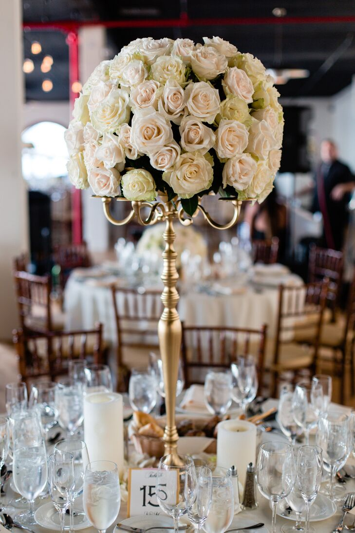 Round arrangements of blush roses sat atop tall golden candelabras in the center of the reception dinner tables. Various sized pillar candles surround the floral accents.