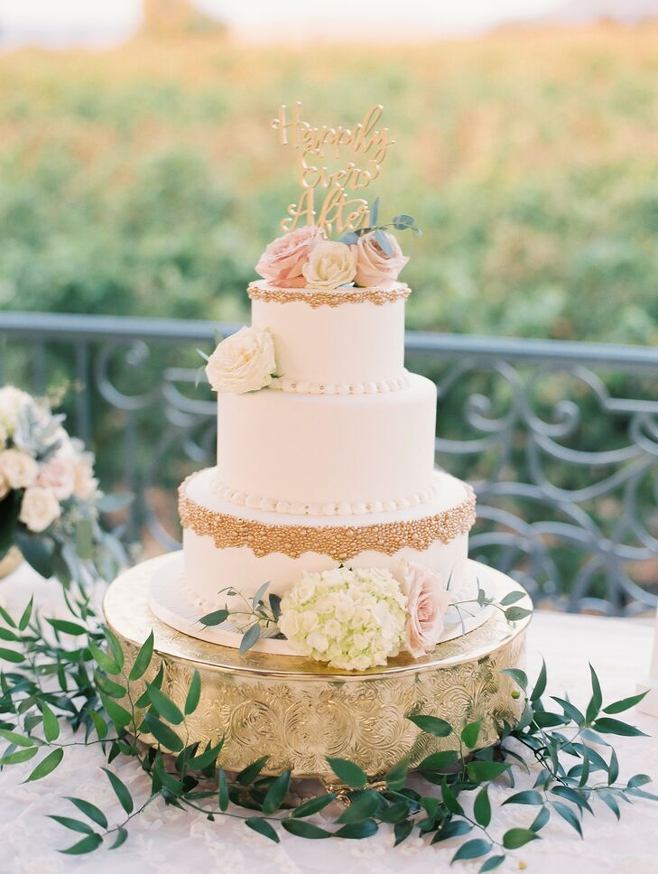 "A three-tier cake with ivory frosting, gold pearl accents and flowers was topped with a gold ""Happily Ever After"" cake copper, a nod to Andrea's love for Disney fairy tales."