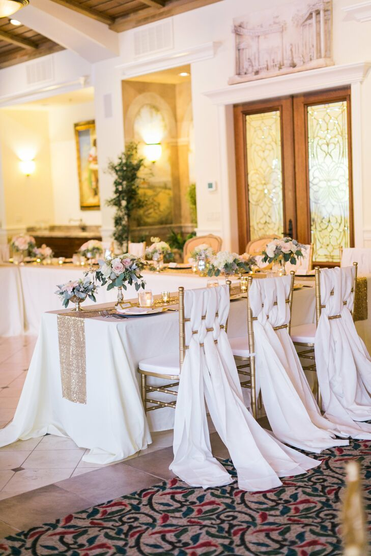 Tables were dressed in ivory linens and gold table runners and adorned with arrangements of blushing bride proteas, cafe au lait dahlias, and vintage blush roses that were displayed in an assortment of vintage vases.