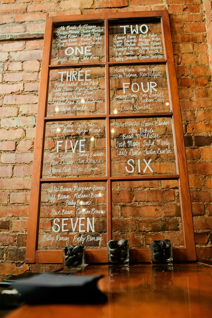 The bride and groom painted their guest's seating assignments on a repurposed window.