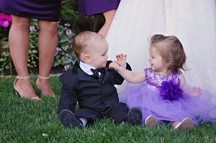 The flower girl wore a tutu-style purple tulle dress. The bodice was accented with sequins to match the sparkly theme of the wedding. She also wore a plum tulle flower around her waist to match the bridesmaids' dresses. The ring bearer wore a classic three-piece black suit complete with a black bow tie.