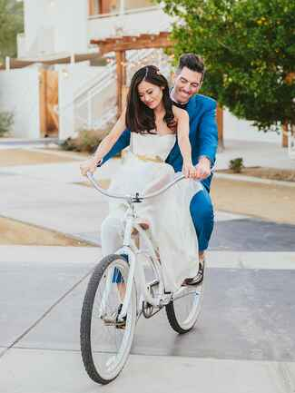 Couple leaving wedding on a bike