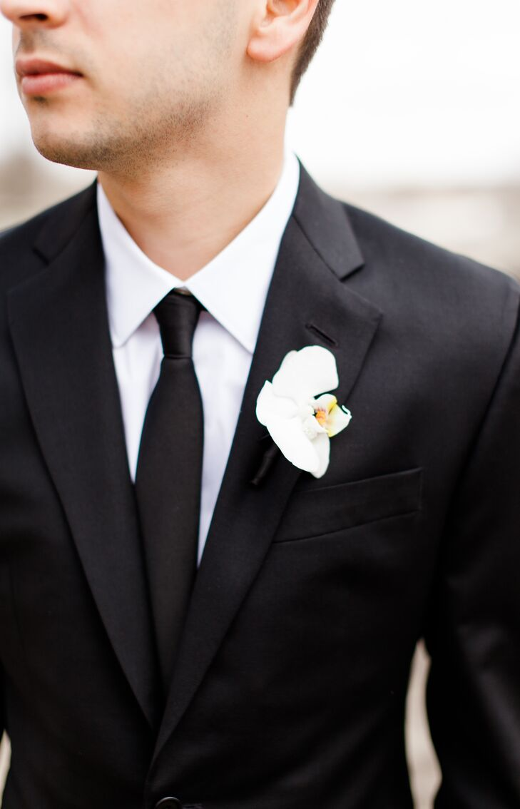 Tyler had a single white orchid pinned to the lapel of his black suit jacket, matching Jenna's bouquet of white hydrangeas and orchids. Tyler's arrangement stood out from the groomsmen's boutonnieres, which consisted of green succulent boutonnieres.