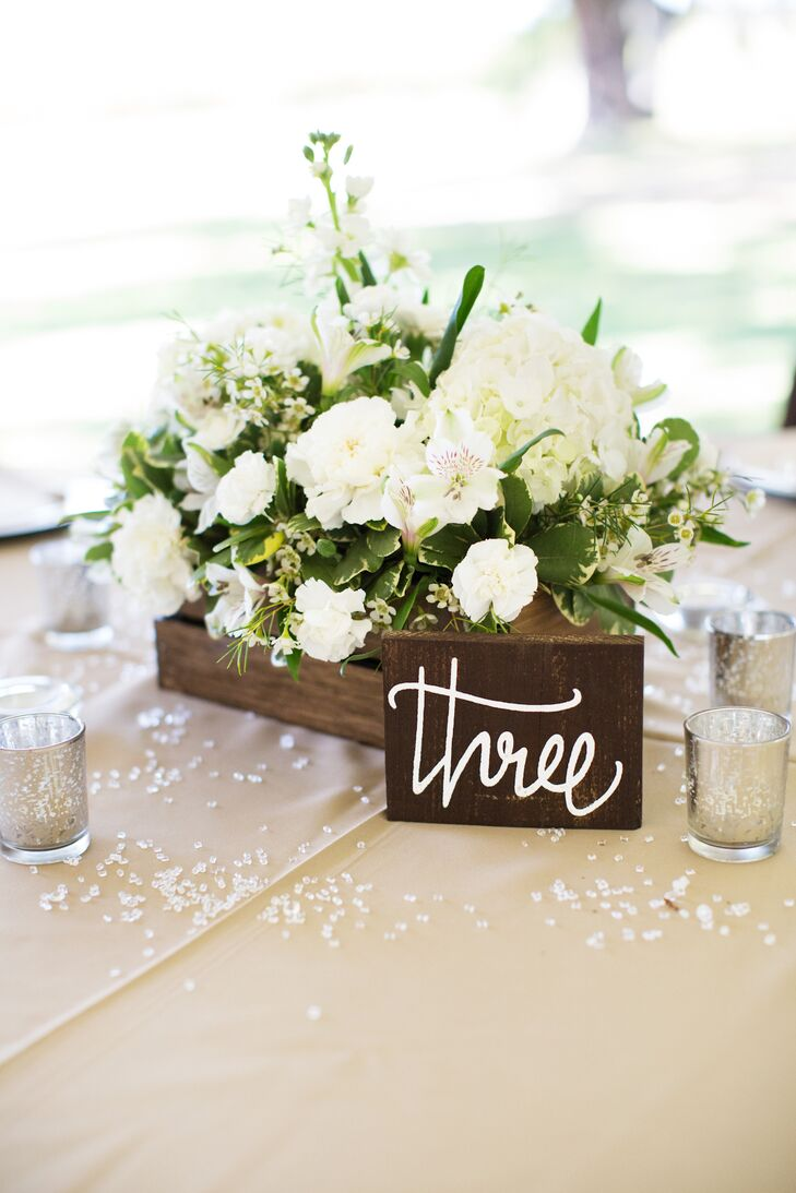 The reception tables were topped with white hydrangeas, alstromerias and wildflowers in rustic wooden boxes. Erin and Buddy loved how the natural palette matched the plantation's natural beauty and how the overgrown centerpieces brought the outside in.