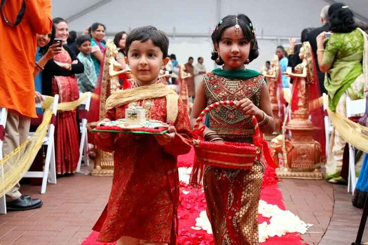 Ring bearer and flower girl dressed in red
