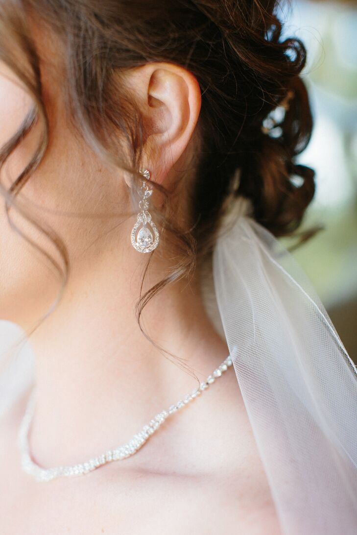 Kellie wore a dangling pair of teardrop earrings accented with crystals and an elegant thin silver necklace. The two pieces of jewelry went with the crystal accents that were seen throughout her wedding dress silhouette.