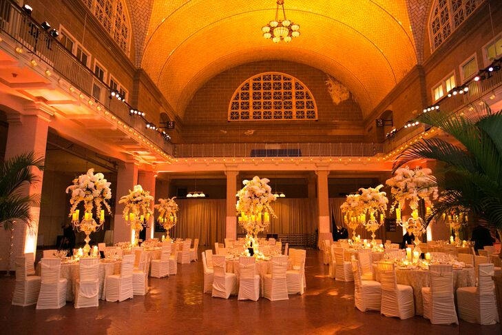 As guests made their way into the Registry Room for the reception at Ellis Island in New York City, they were immediately blown away by the transformation. Warm uplighting and skyward-reaching arrangements of full blooms introduced an element of drama to the historic room, while soft candlelight created a feel of undeniable romantic ambiance. Gilded dinnerware, crystal accents and rose-tufted cream linens had a luxe vibe that achieved the glamorous, old-Hollywood feel the couple were after.