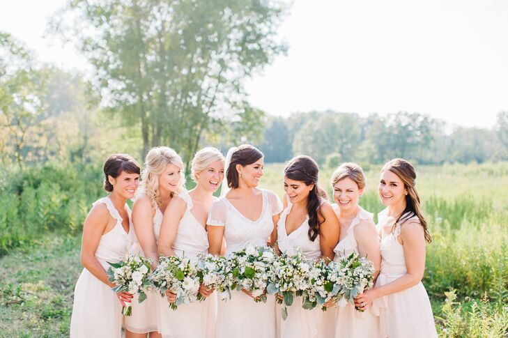 "Anna chose ivory Joanna August dresses for each of her bridesmaids thanks to the casual design of each. ""Since the venue was outside, I wanted the girls to be comfortable,"" she says. The group completed their wedding day style with gold initial charm necklaces gifted to them by the bride."