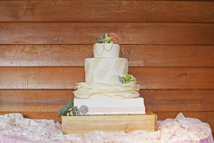 Miranda and Eric's four-tier wedding cake beautifully represented their natural style. It had smooth, modern details, ruffles, vintage lace appliques and even pearls draped across the top tier, with a brooch and flowers to accent.