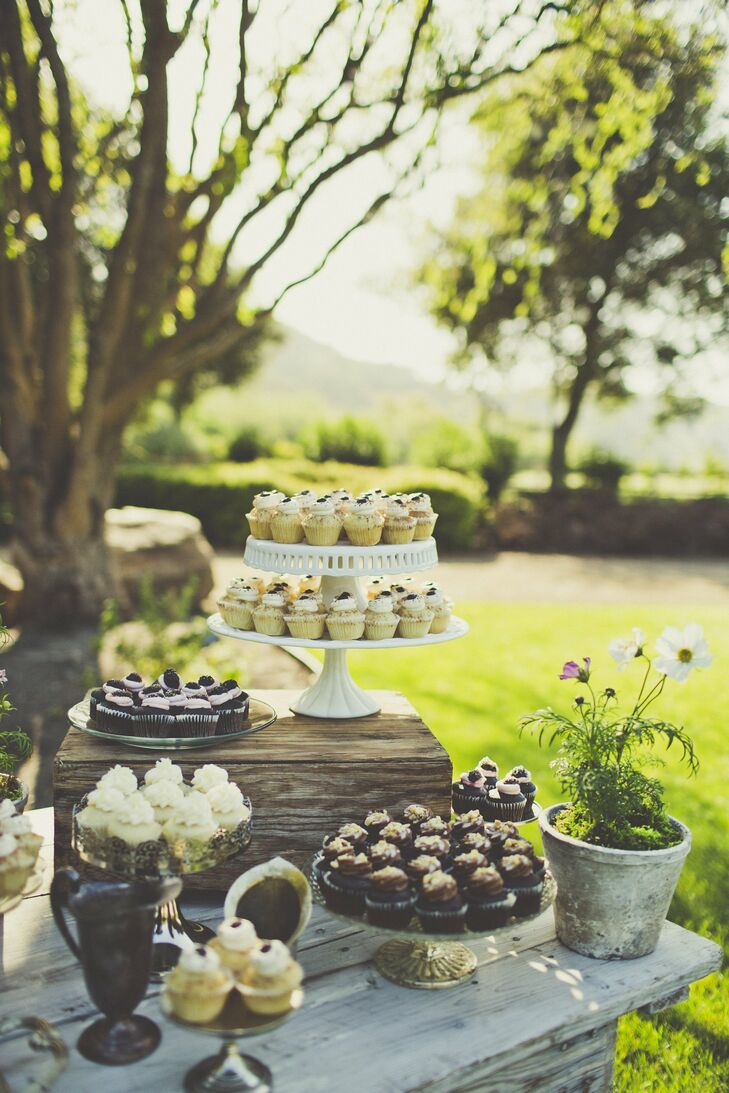 Cupcakes in an assortment of flavors were set out on an eclectic collection of vintage-inspired cake stands.