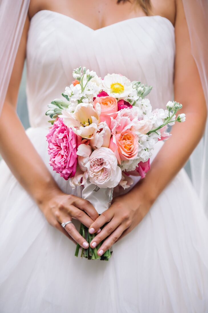 While Caroline's wedding dress and accessories were all ivory and silver, she added a pop of color with her bouquet. Events by Nouveau, their florist, filled its ivory satin wrap with blush and fuchsia garden roses, white delphiniums, peach roses and white tulips.
