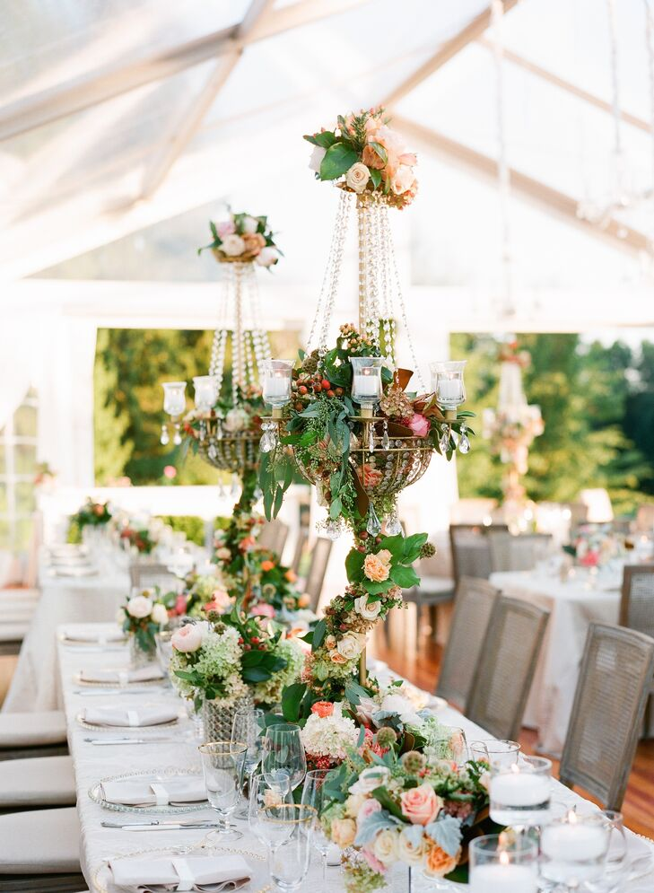 "The reception took place under an expansive tent at The Wheatleigh in Lenox, Massachusetts, providing guests with picturesque views during dinner. ""One of the best things about having a tented reception space is that it gives you a blank canvas to create the atmosphere you want,"" Katie says. The tables were adorned with three-foot chandelier candelabras decorated with garlands of textured florals styled alongside smaller arrangements that ran the length of the table and flickering golden candlelight."