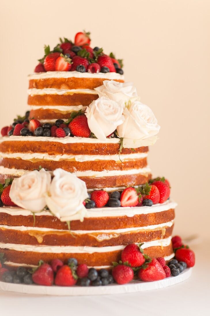 The bride and groom cut into a three-tier orange blossom and lemon curd cake layered with beautiful fresh summer berries.