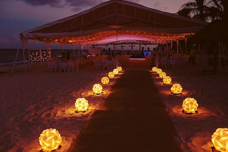 Spheres of lights on the sand led the way to Marta and Jose Luis's dance-party reception, which took place under a waterfront tent at Le Reve Hotel and Spa in Playa del Carmen, Mexico.