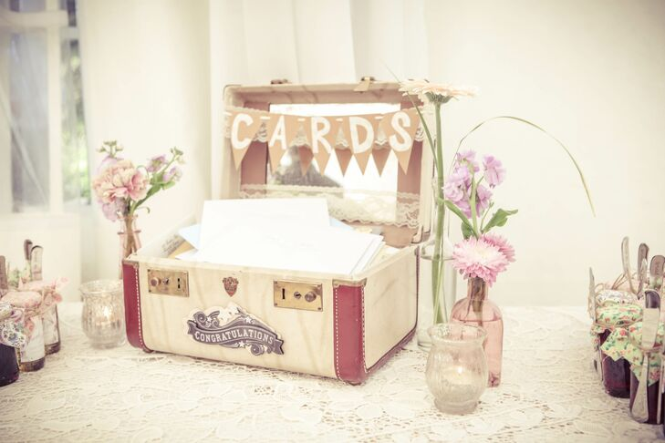 Guests left cards for the couple in a vintage suit case surrounded by pastel flowers.
