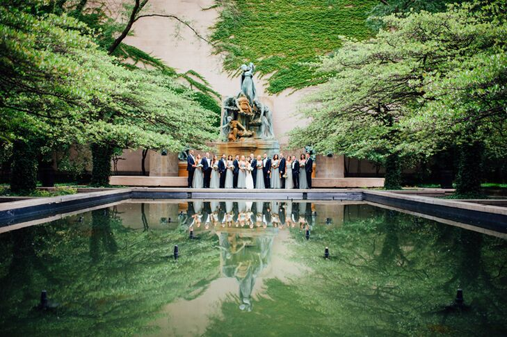 The wedding party posed in front of the reflecting pool and Fountain of the Great Lakes statue in the South Garden of the Art Institute of Chicago.
