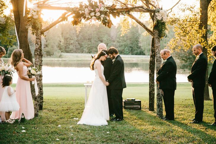 Bride and groom standing under a handmade arbor with their heads bowed