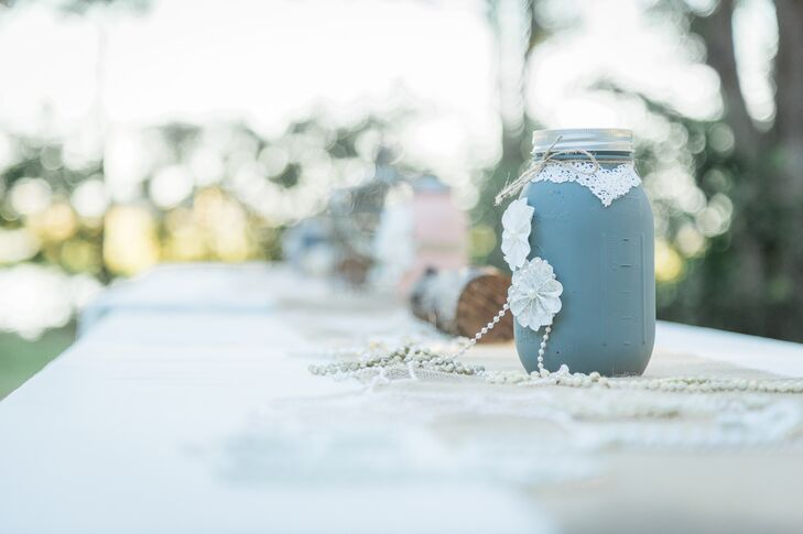 Tangie and Mike painted mason jars in the wedding colors—light gray, blush and ivory—to decorate the reception tables. To add a little romance to the look, the couple added lace and strands of pearls to each one. They loved having handmade details throughout the decor to add an ultra-personalized feel.