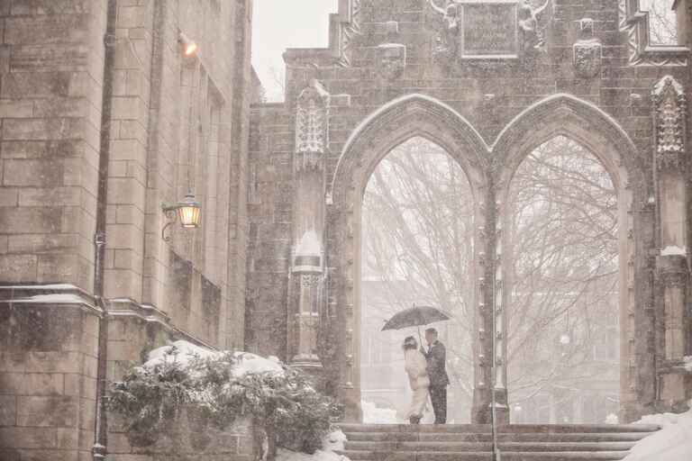 Couple surrounded by falling snow at their winter wedding