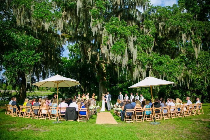 Carly and Spencer's wedding ceremony was held under oak trees along the Ashley River. The ceremony was personalized with handwritten vows and was officiated by the couple's friend.
