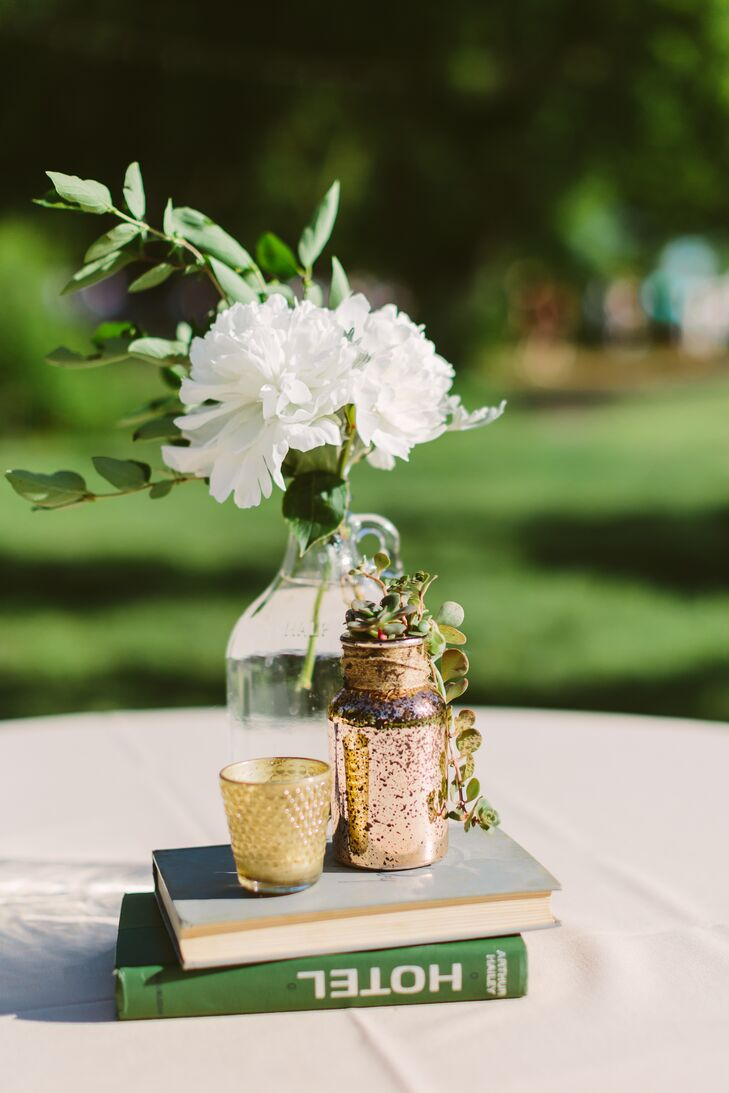 Ivory chrysanthemums and green leaves arranged inside glass jars sat on top of a vintage stack of books, positioned next to another vase and votive candle.