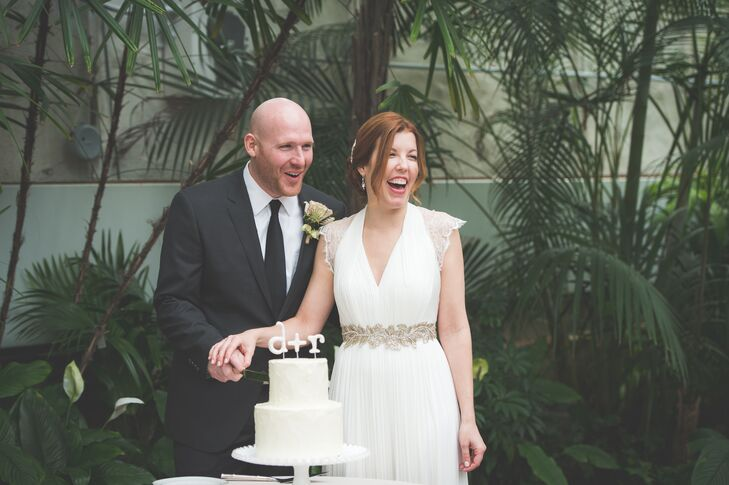 The couple stood behind their two-tiered ivory wedding cake, decorated with a topper of the couple's initials.